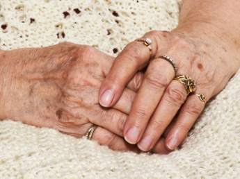 Senior woman's crossed hands with age spots over an off white knitted blanket, seems to be waiting.