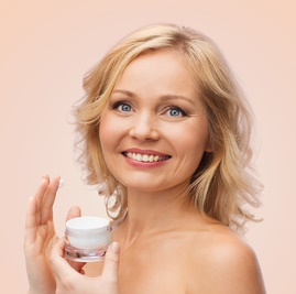 happy woman applying cream to her face