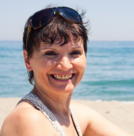 Portrait of happy middle aged woman relaxing on the beach.